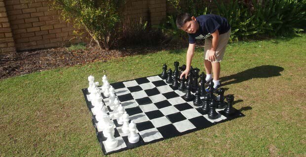 Boy Playing With Giant Chess Set on Grass