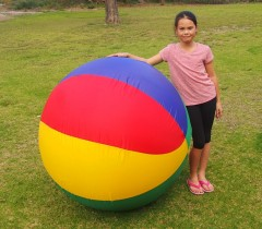 Girl Standing Next to Giant Inflatable Ball in Park