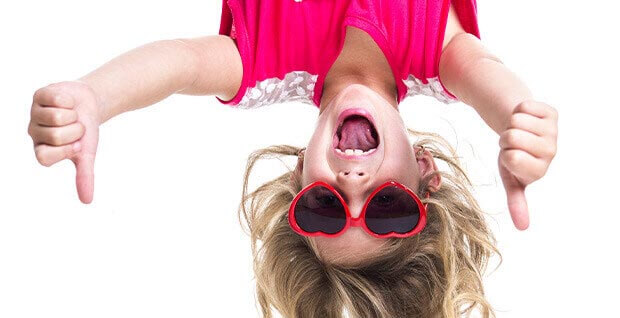 Child With Sunglasses Hanging Upside Down With Thumbs Up