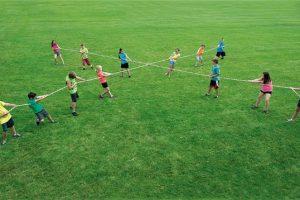 13 People Playing 4 Way Tug Of War on Grass Field