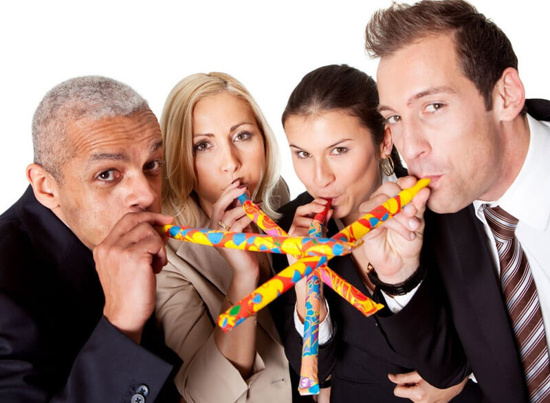 4 People In Suits Blowing Into Party Blowers