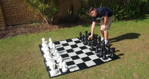 Boy Playing With Giant Chess Set in Garden