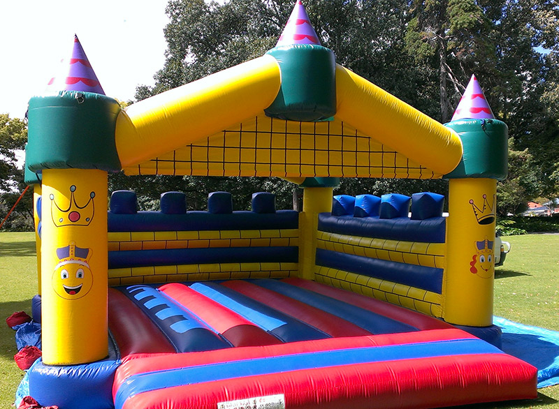 Yellow, Blue and Red Bouncy Castle Setup on Grass Oval