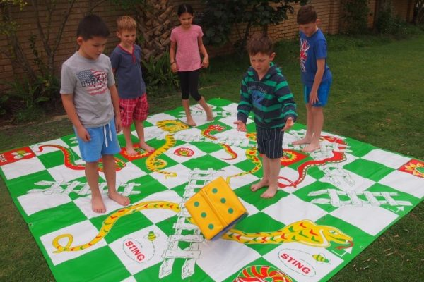 Children Playing Giant Snakes and Ladders in Garden