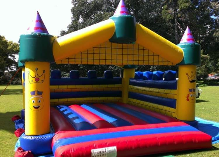 Yellow, Red and Blue Bouncy Castle Setup on Grass