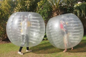 2 People Playing in Inflatable Zorb Balls on Grass