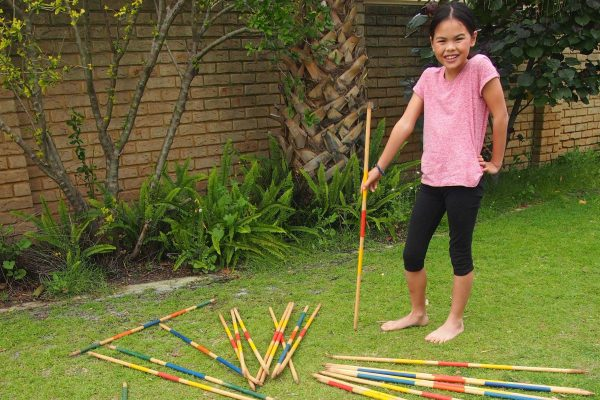 Girl Playing Pick-up-sticks Game on Grass