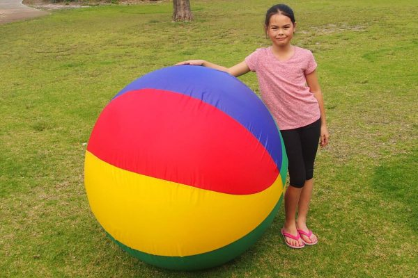 Girl Standing Next to Giant Inflatable Ball