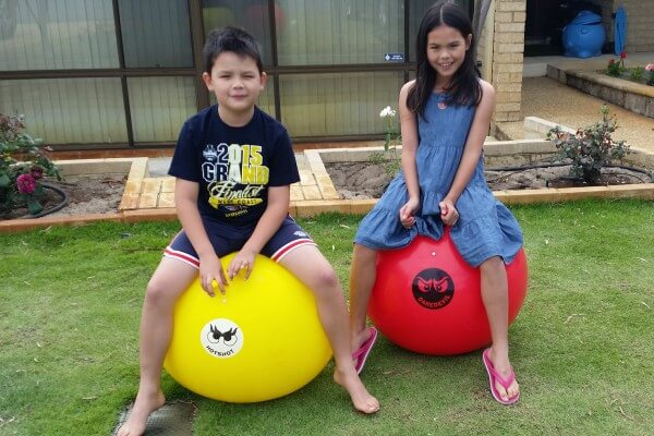 2 Children Sitting on Hopping Mad Inflatables