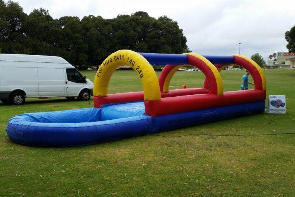 Inflatable Slip n Slide Setup on Grass With Van in Background