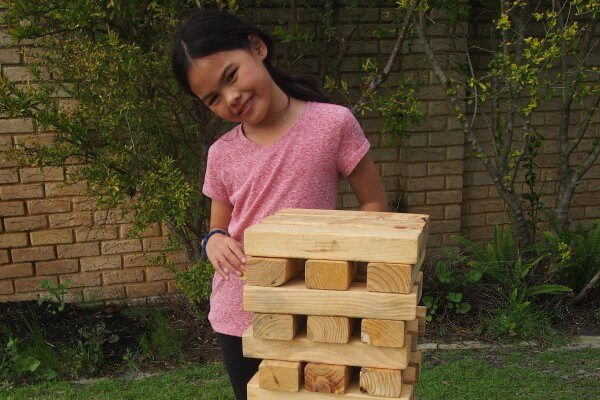 Girl Standing Next to Hi Tower Blocks Game