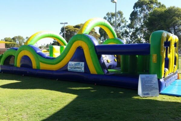 Side View of Inflatable Radical Run Obstacle Course Setup on Grass