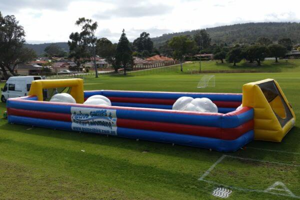 Red, Blue and Yellow Inflatable Bubble Soccer Arena on Grass Field