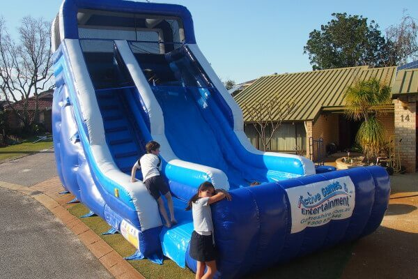 2 Children Next to Blue Wave Inflatable Water Slide on Grass