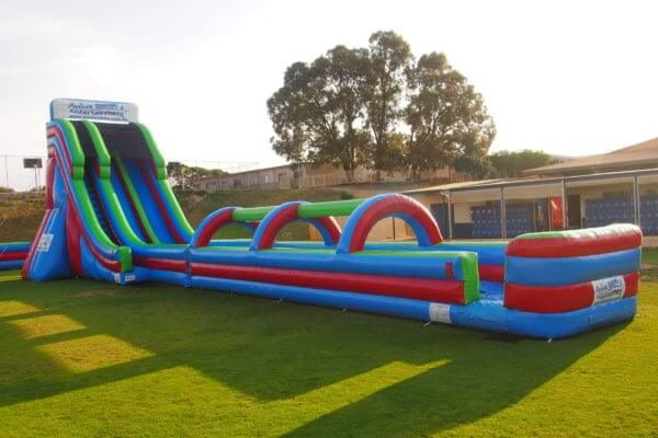Side View of 2 Lane Inflatable Mega Water Slide on Grass Oval
