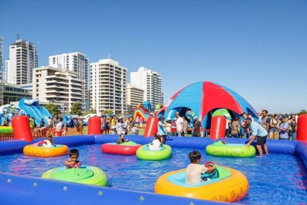 Children in Inflatable Boat Pool with City Background